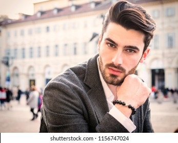 Handsome serious businessman standing outside in elegant European city center, Turin in Italy