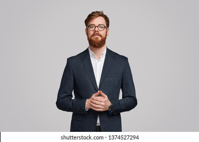 Handsome serious Irish businessman with ginger beard clasping hands and looking at camera against gray background