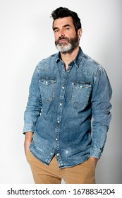 Handsome serious man with light eyes, beard, with shirt and jeans on white background in photo studio.