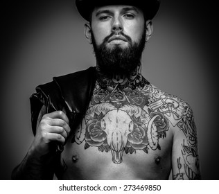 Handsome serious man with tattooed body