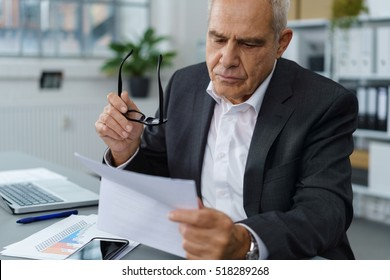 Handsome serious mature businessman in dark blazer and white shirt checking forms while holding eyeglasses