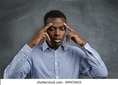 Handsome serious puzzled African student dressed in checkered shirt robbing his forehead, closing his eyes, looking concentrated and focused, trying to remember right answer during test in classroom