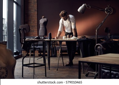 Handsome serious tailor in white shirt with brown leather suspenders working near wooden table with threads, apron and scissors in amazing atelier with antique furniture and mannequin on background