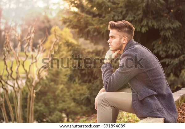 Handsome serious young man outdoors thinking, looking to the distance, pondering