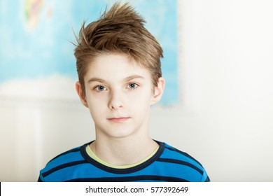 Handsome serious young preteen boy posing in front of a map on the wall in his bedroom looking thoughtfully at the camera