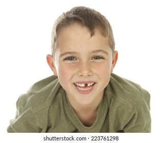 Handsome seven year old boy on a white background with a missing front tooth.