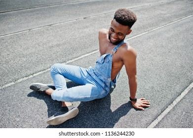 Handsome sexy african american bare torso man at jeans overalls sitting at stadium racecourse. Fashionable black man portrait.