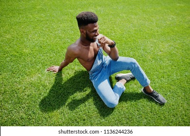 Handsome sexy african american bare torso man at jeans overalls sitting at green grass of stadium football field. Fashionable black man portrait.