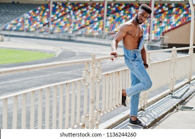 Handsome sexy african american bare torso man at jeans overalls posed at stadium. Fashionable black man portrait.