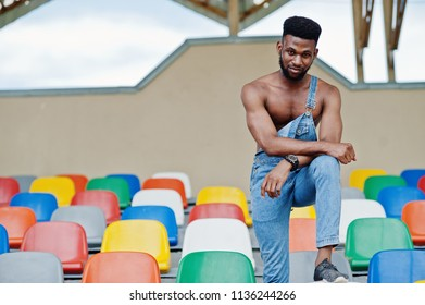 Handsome sexy african american bare torso man at jeans overalls posed on colored chairs at stadium. Fashionable black man portrait.