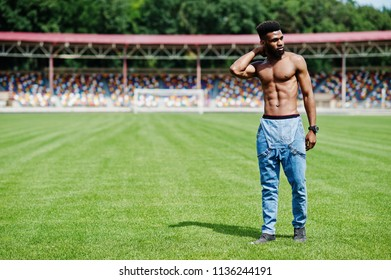 Handsome sexy african american muscular bare torso man at jeans overalls posed at green grass of stadium football field. Fashionable black man portrait.