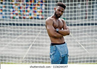 Handsome sexy african american muscular bare torso man at jeans overalls posed at green grass agasinst football gates of stadium field. Fashionable black man portrait.