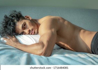 A handsome and sexy arabian or indian male model with big muscles and a good body with strong biceps and a cute face with curly brown hair, is laying sensual at his pillow in his bed
