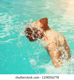 Handsome sexy bearded man with tattoo swimming in pool with blue water and drops sunny summer day outdoor. Funny boy jumping out of water like dolphin.