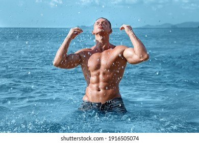 Handsome sexy fitness wet young man with athletic body and naked torso in blue jeans is kneeling in the ocean and splashing water. Fitness tanned guy enjoying summer