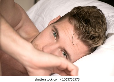 Handsome, sexy good looking man with green eyes first thing in the morning, looking at camera in a bed with white sheets