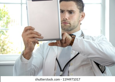 Handsome, sexy, male doctor, gp, in white lab coat holding and using digital tablet