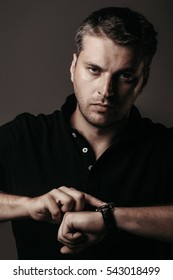 handsome sexy man or guy with stylish hair on serious unshaven face in shirt with watch on hand on grey background, closeup