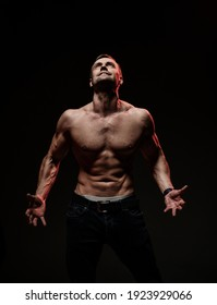 Handsome sexy man with muscular body, showing a welcome gesture, standing on a black background. Sports, bodybuilding motivation. Dark studio shot with copy space portrait