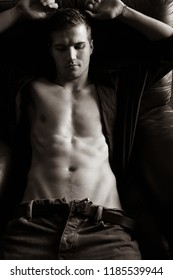Handsome, sexy man with muscular defined, six pack abs sitting on leather armchair