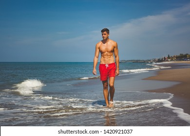 handsome sexy man in red shorts and with naked tanned fit torso walks on beach along the ocean. bright blue water and sky