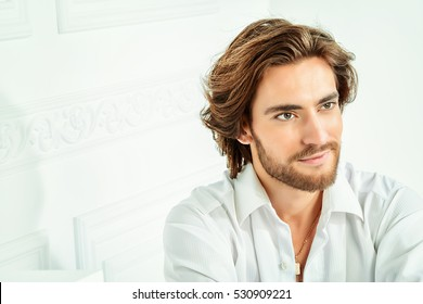 Handsome sexy man wearing white shirt posing in luxurious interior. Men's beauty, fashion model. Hair styling.