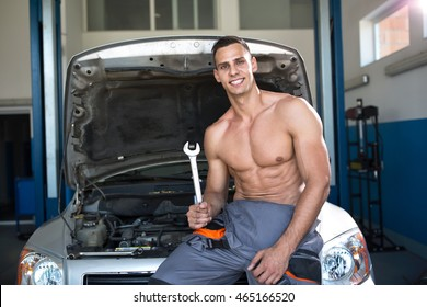 Handsome sexy muscular mechanic with a tool at the work