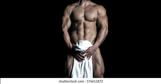 Handsome sexy muscular naked / nude bodybuilder body on a black background.