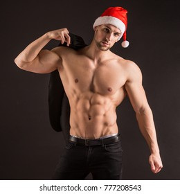 Handsome sexy santa claus guy on black background