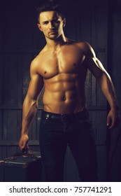 Handsome sexy sensual muscular stylish young man topless with bare torso and beautiful body standing near stairs with hard big retro suit case indoor on wooden background, vertical picture