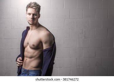 Handsome, sexy and shirtless male model looking into camera. Fashionable young man against white brick background. Strong, athletic and muscular guy with six pack abs.