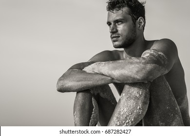 Handsome sexy topless male model relaxed sitting on the beach. Black and White.