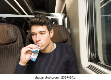 Handsome sexy young man on a train sitting in his passenger seat eating a cereal bar for a healthy snack and looking off to the side with a serious expression