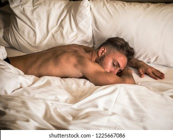 Handsome shirtless athletic young man laying in bed at night with eyes closed, sleeping