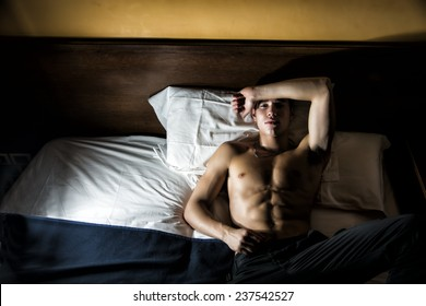 Handsome shirtless athletic young man laying in bed at night looking at camera