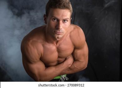 Handsome shirtless bodybuilder shot from above, standing on dark background wearing trunks