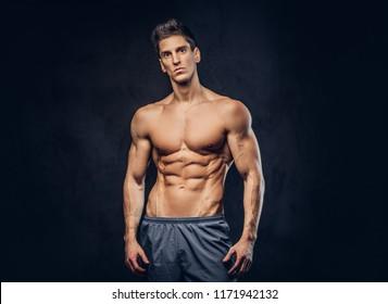 Handsome shirtless ectomorph bodybuilder with stylish hair posing on a dark background.