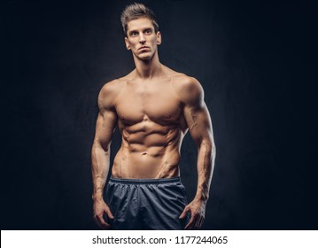 Handsome shirtless ectomorph bodybuilder with stylish hair posing on a dark background.