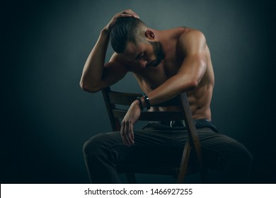 Handsome Shirtless Male Fashion Model Sitting on a Chair