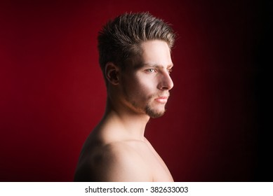 Handsome shirtless male model against a red background