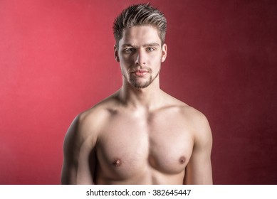 Handsome shirtless male model against a red seductive background. Cute young man looking confident into camera.