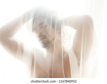 Handsome shirtless man behind a curtain