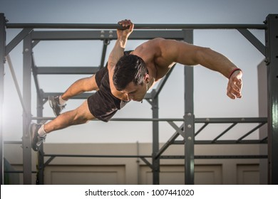 Handsome shirtless man having calisthenics training on horizontal bar outdoors.