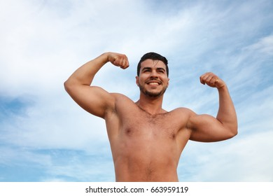 Handsome shirtless man on the beach in the summer day
