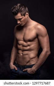 Handsome shirtless man posing on black studio background.