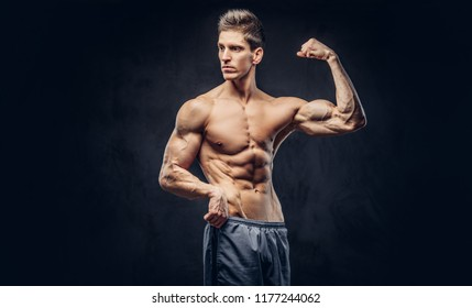 Handsome shirtless man with stylish hair and muscular ectomorph shows his bicep on the dark textured background.