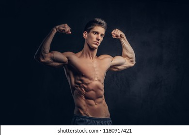 Handsome shirtless man with stylish hair and muscular ectomorph shows his biceps.