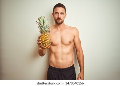 Handsome shirtless man wearing swimwear and holding pineapple isolated background with a confident expression on smart face thinking serious