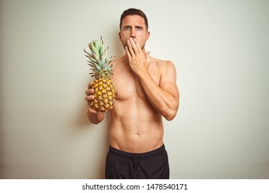 Handsome shirtless man wearing swimwear and holding pineapple isolated background cover mouth with hand shocked with shame for mistake, expression of fear, scared in silence, secret concept
