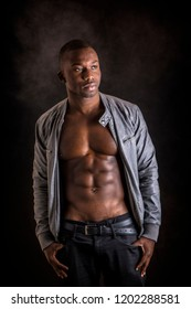 Handsome shirtless muscular black young man's with jacket open on naked torso, looking at camera, on dark background in studio shot